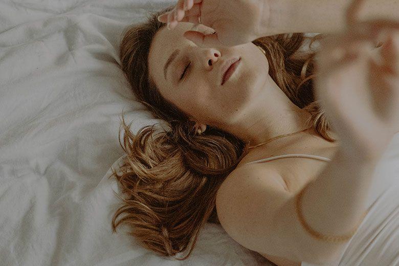 Auf dem Rücken liegende blonde Frau auf dem Bett