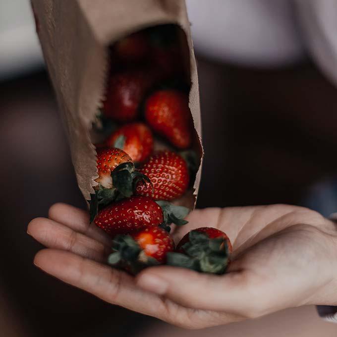 Hand mit einer Tüte Erdbeeren