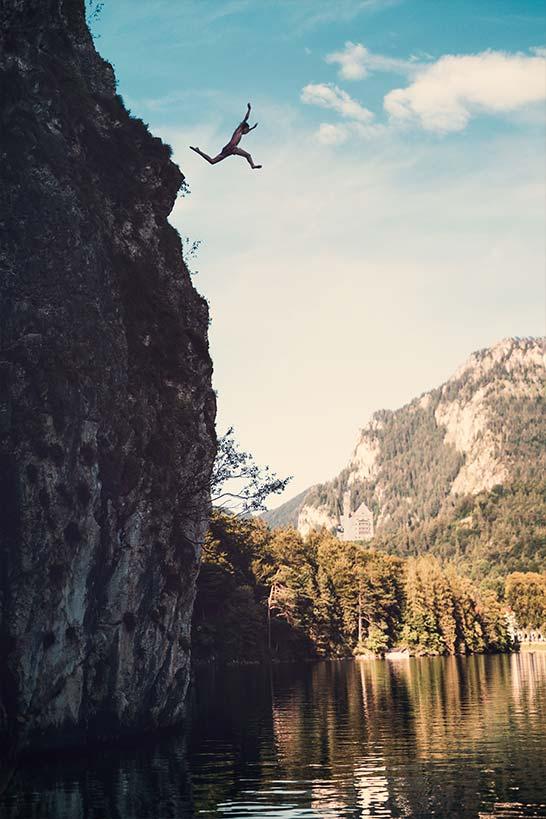 Mann springt von Felsen in Bergsee