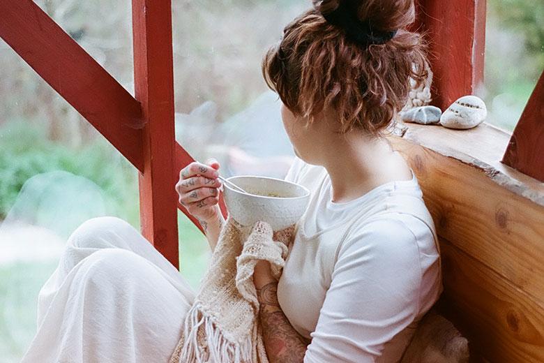 Auf Holzbank sitzende Frau mit Teetasse in der Hand