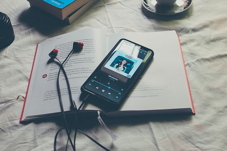 Smartphone mit Kopfhörern auf einem aufgeschlagenen Buch