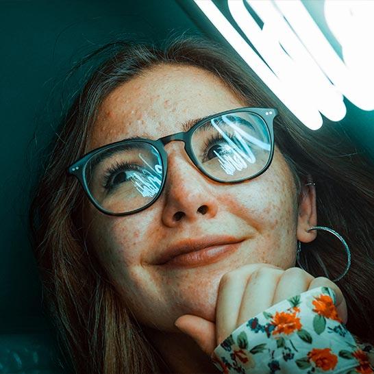 Schmunzelnde, dunkelhaarige Frau mit Brille