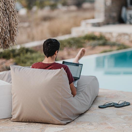 Vorm Pool liegender Mann mit Laptop auf dem Schoß