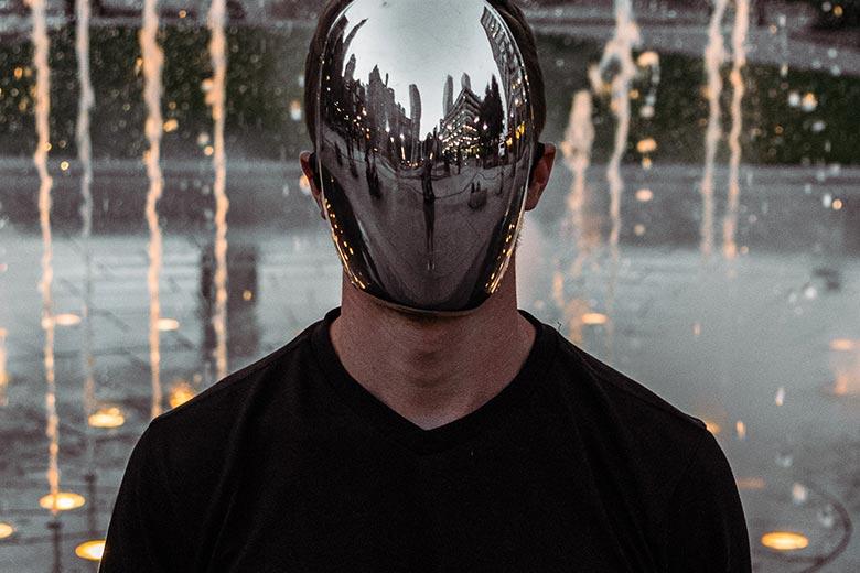 Mann mit Spiegelmaske vorm Gesicht