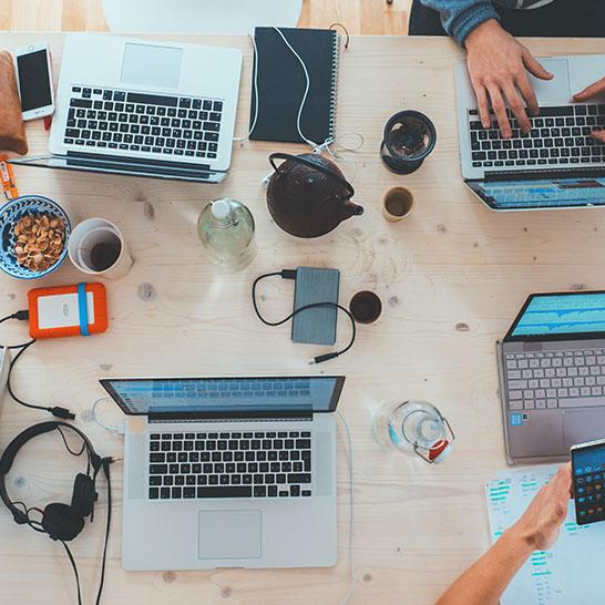 Fünf Laptops sowie Smartphones, Tablets und weitere Tools auf Schreibtisch
