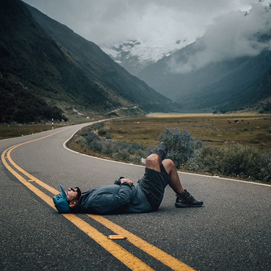 Mann, der mitten auf einer unbefahrenen Landstraße liegt