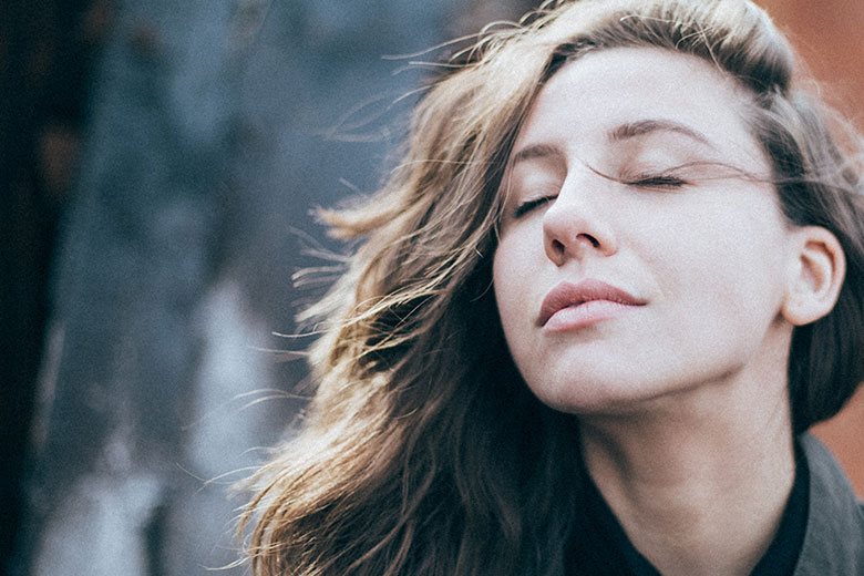Langhaarige Frau, die mit geschlossenen Augen ihr Gesicht in den Wind hält