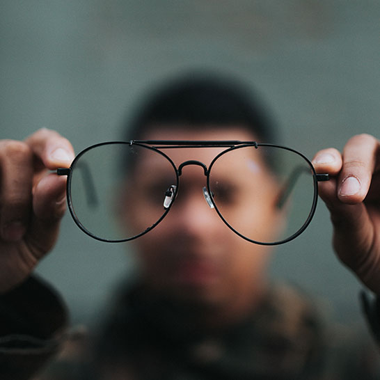 Mann, der Brillengestell in die Kamera hält