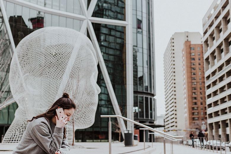 Telefonierende Frau vor Monument in Form eines Kopfes und Glasgebäude