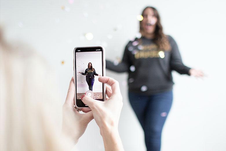Person, die mit dem Smartphone eine junge Frau fotografiert