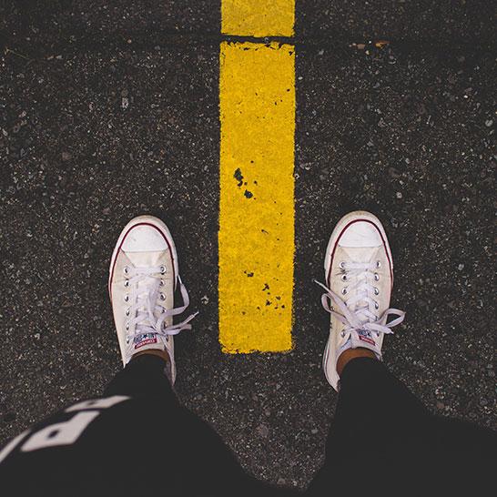 Ausschnitt einer Person, die auf Mittelstreifen einer Straße steht