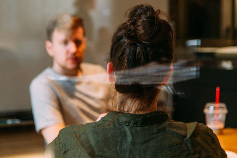 Frau von hinten an Tisch sitzend mit Mann gegenüber