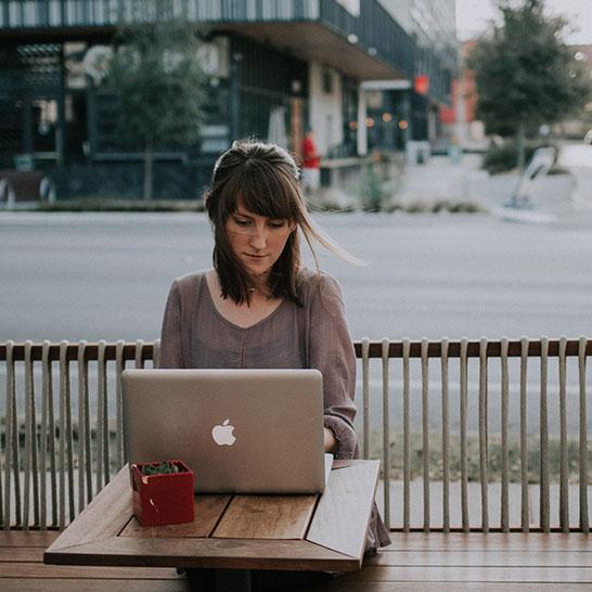 Am Tisch sitzende Frau vor Laptop