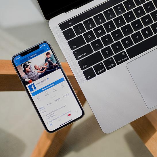 Geöffnete Facebook-App auf Smartphone neben Laptop