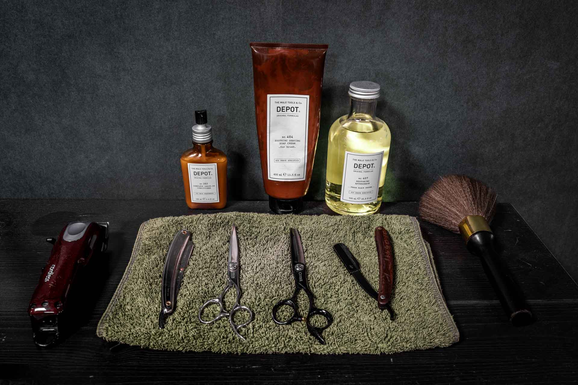 Friseurutensilien von Weltmann Barbershop in Ulm. Schere und Kamm liegen auf dem Handtuch vor Pflegeprodukten