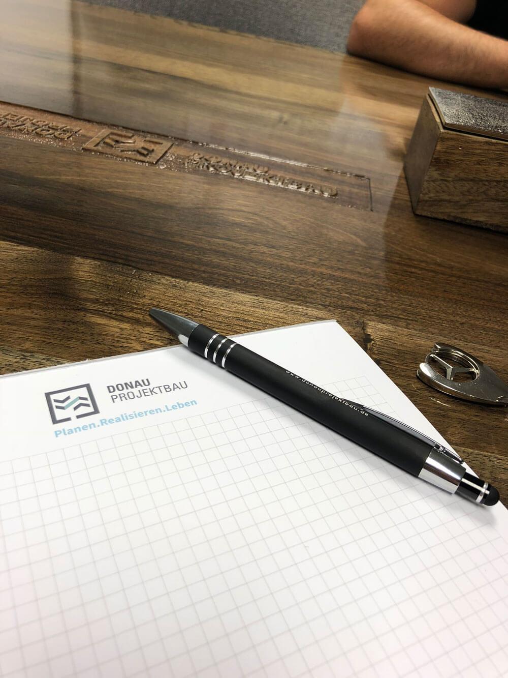 Block mit Logo von Donau Projektbau auf dem Holztisch im Besprechungszimmer.