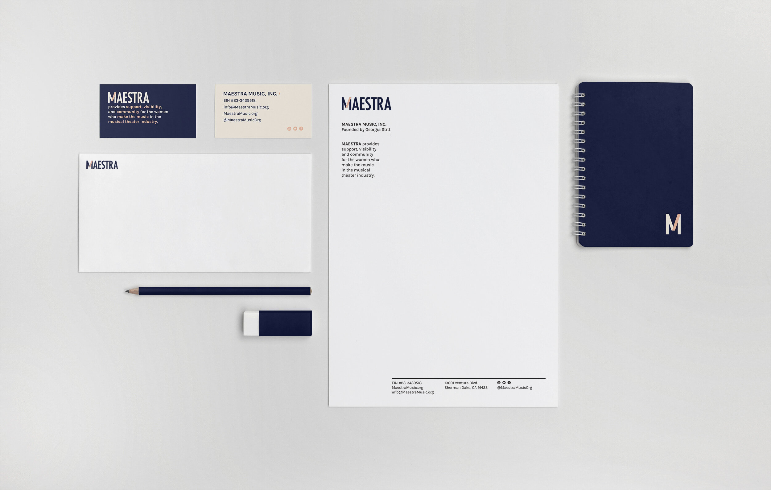 Office supplies with navy branding laid out on a gray background.