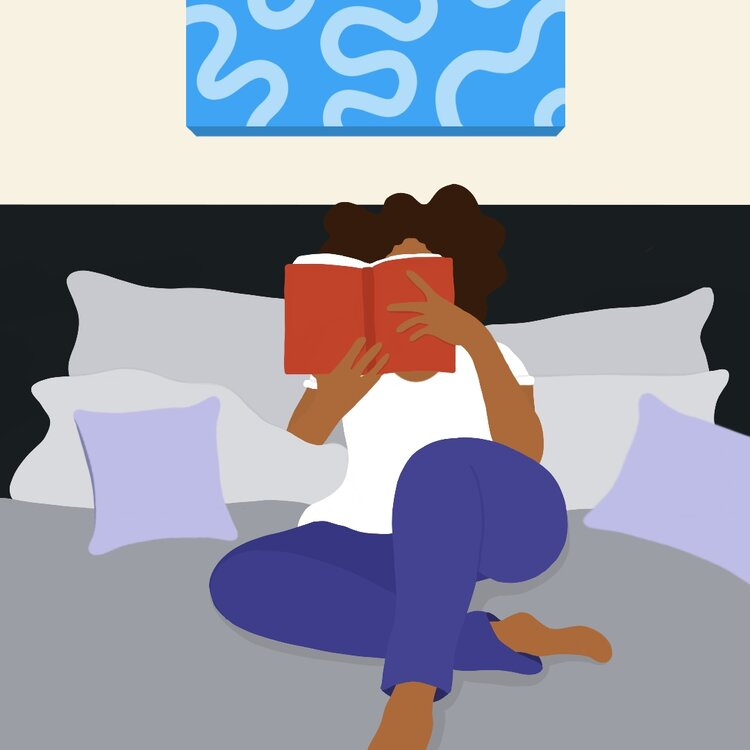 A woman in pajamas lounges on a bed while reading, her face covered by the book.