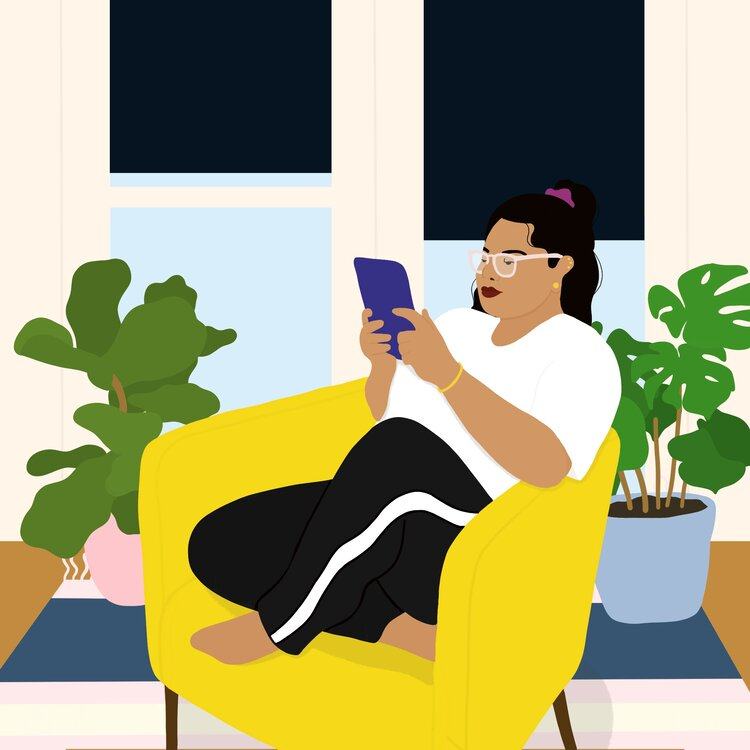 A woman in a yellow chair reads on a tablet in front of plants and windows.
