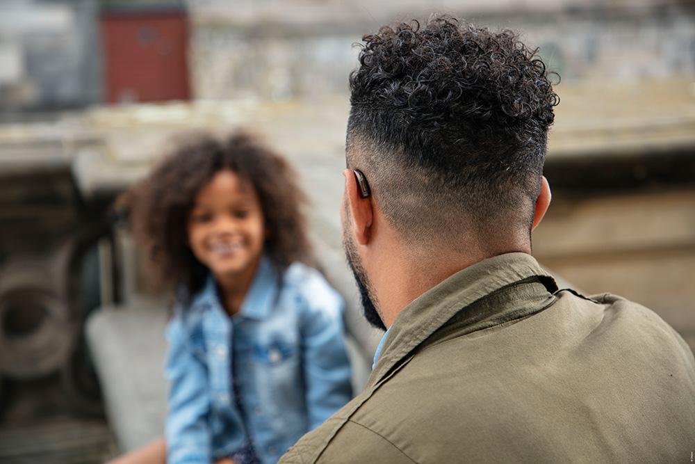 Man weaing hearing aid conversing with a kid