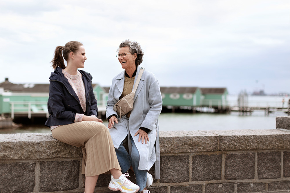 Woman and old woman happily speaking to one another