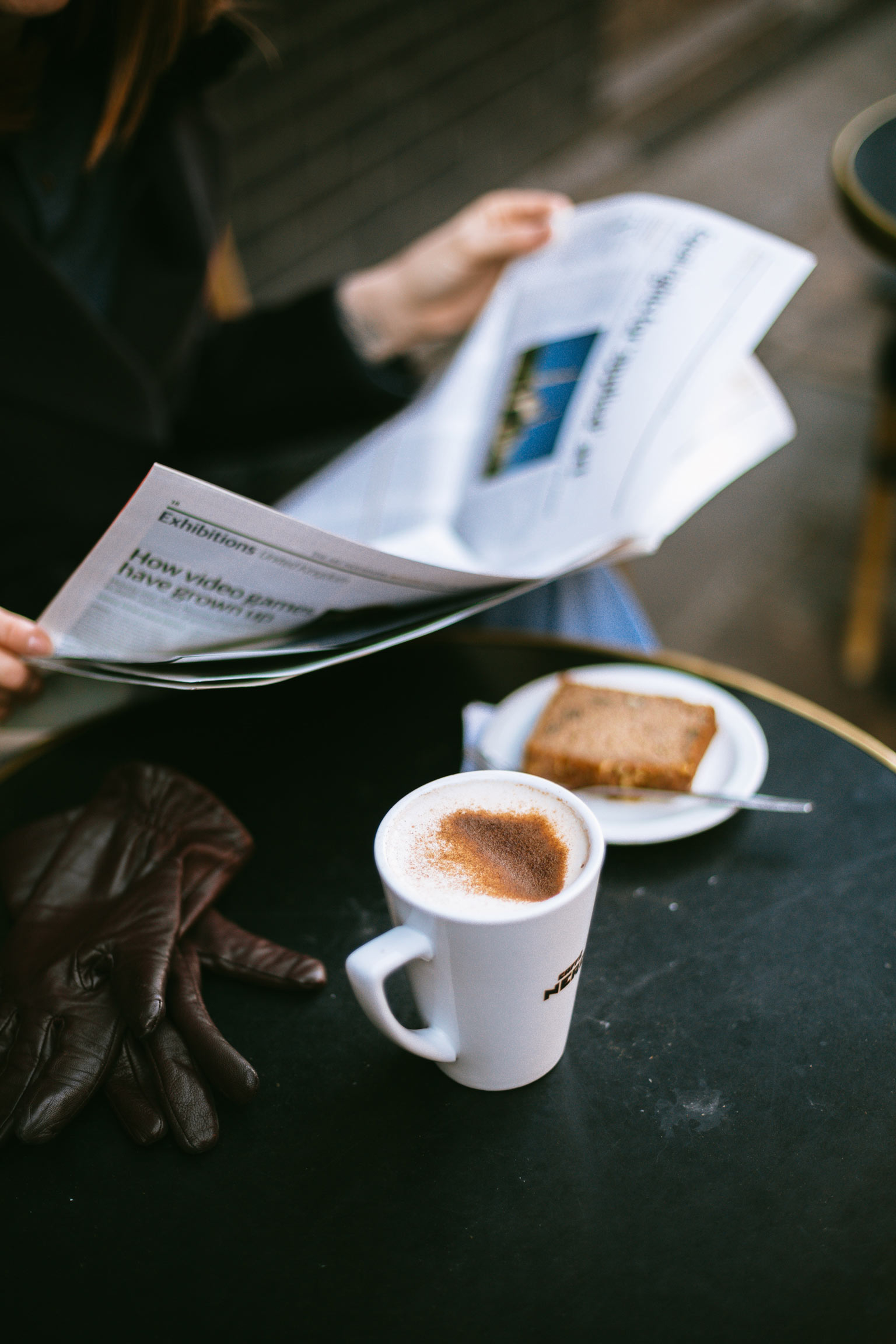 Person reading newspaper with coffee and cake