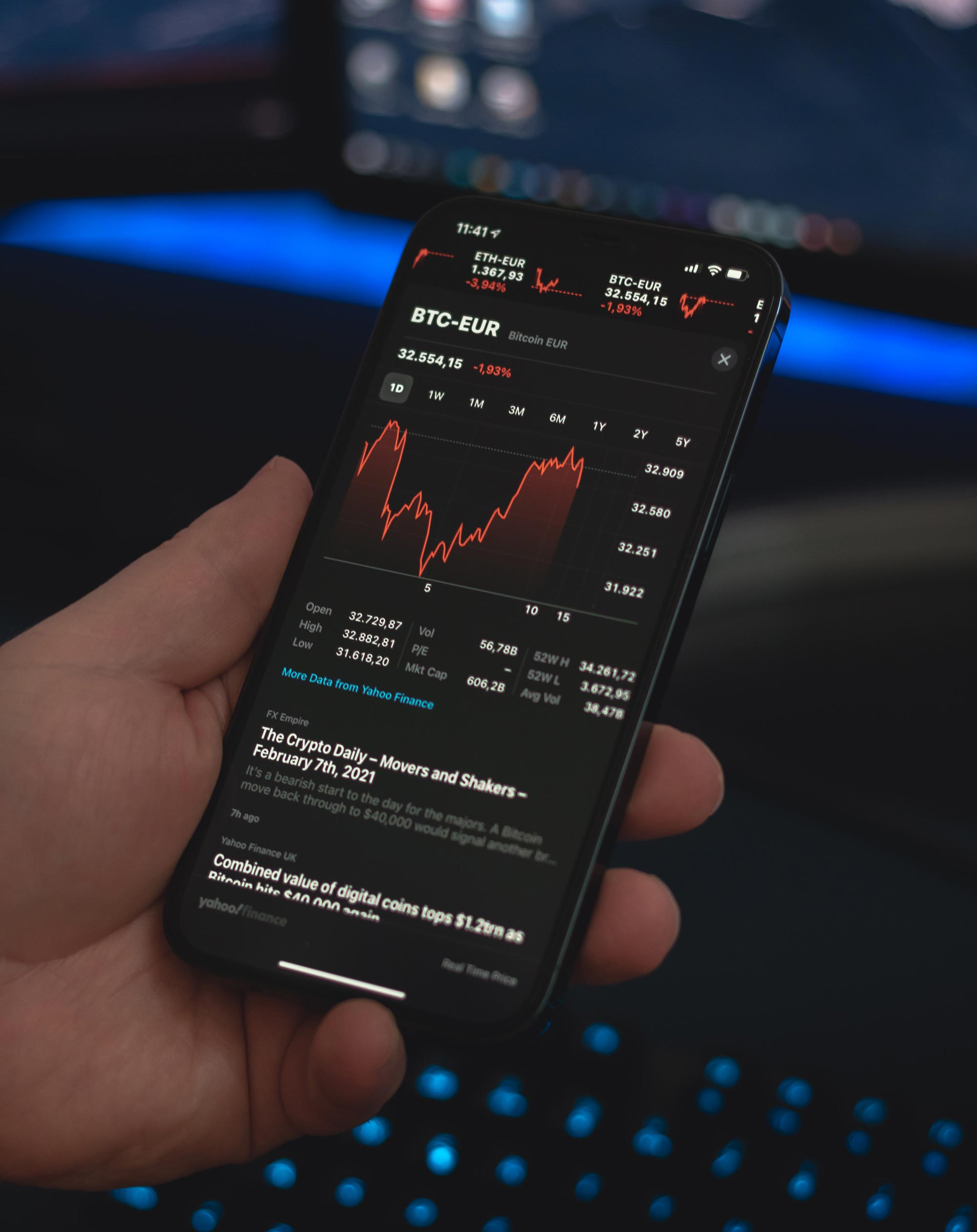person holding an iPhone displaying a cryptocurrency app