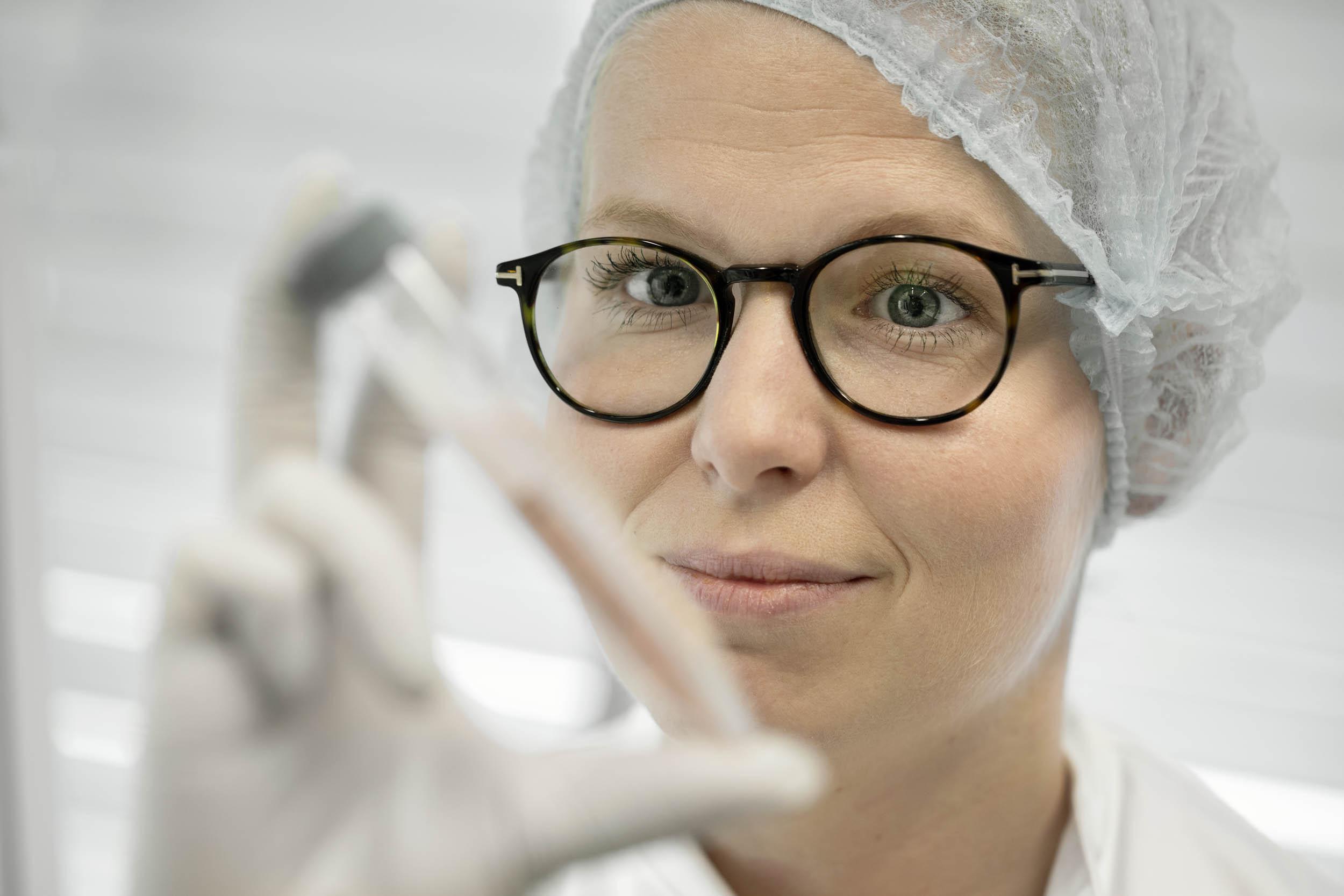 Lab personnel examine test tube with specimen