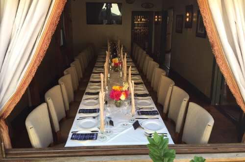 Very large and long tablecloth dining table with seating for over 20 people.