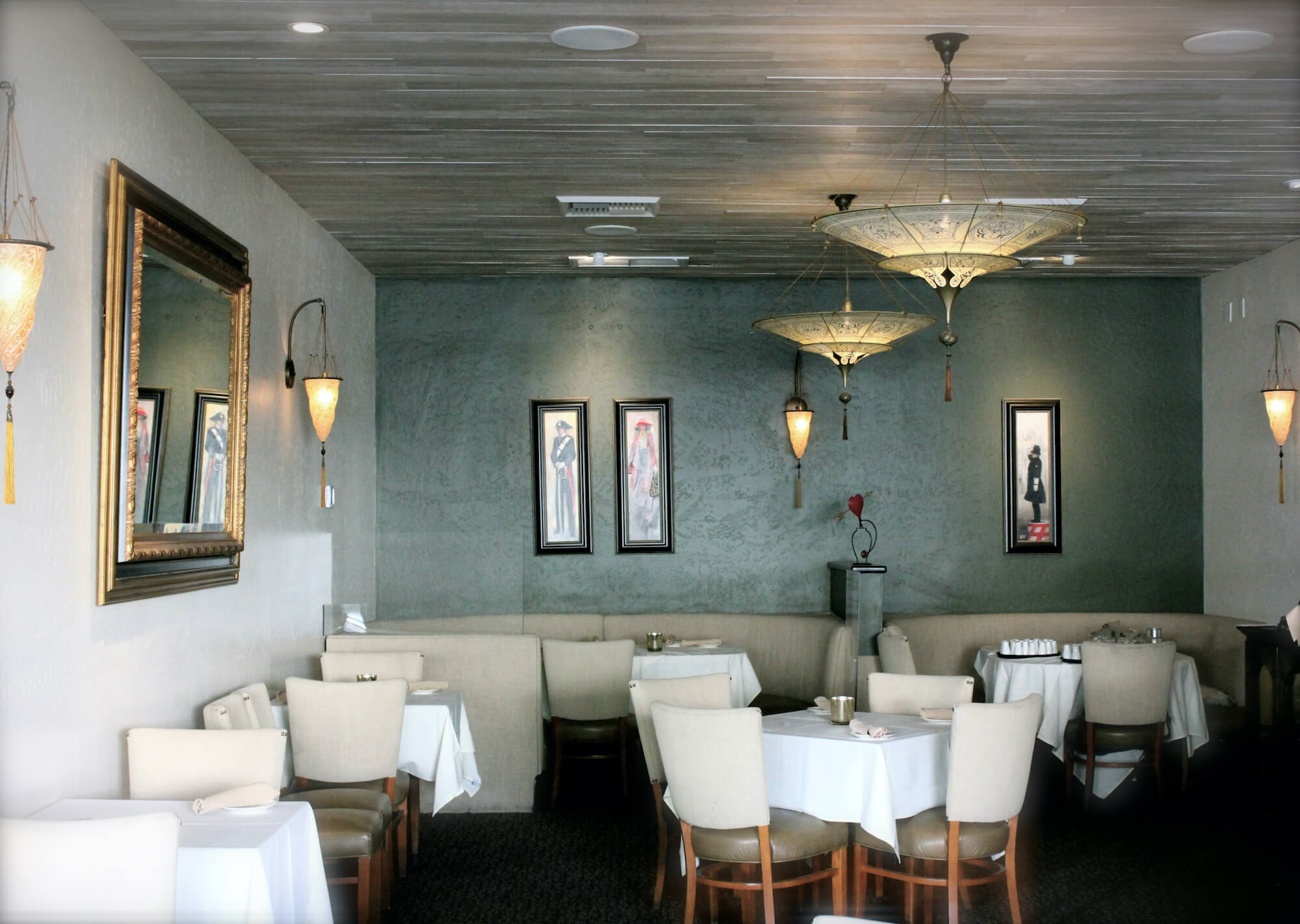 Dining room with sconces and chandeliers in prominent view.