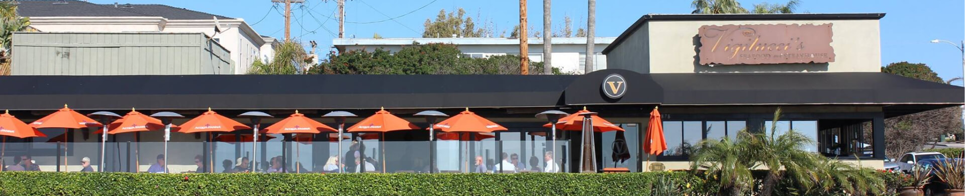 Street view of Vigilucci's restaurant with outdoor umbrella-covered patio visible.