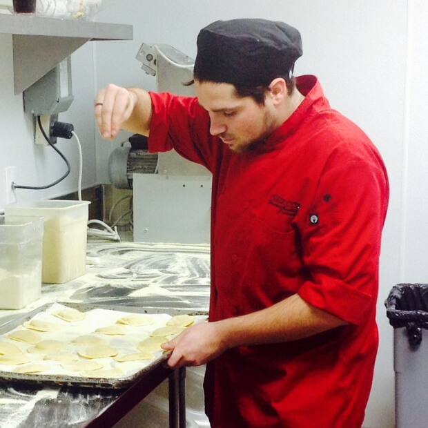 Prep cook in a bright red chef coat making fresh pasta.