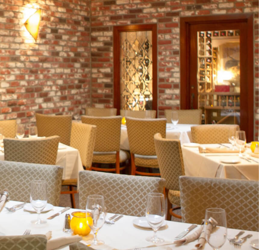 Dining room with brick wall and decorative tablecloths.