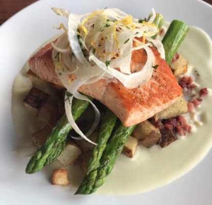 Plate of fish and asparagus over a creamy sauce.
