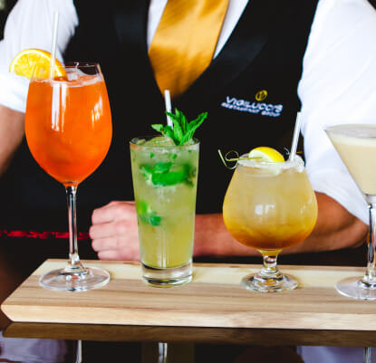 Waiter holding and presenting a board of cocktails.