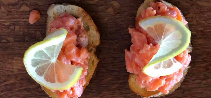 Simple fish ceviche bruschetta with lemon slices on top.