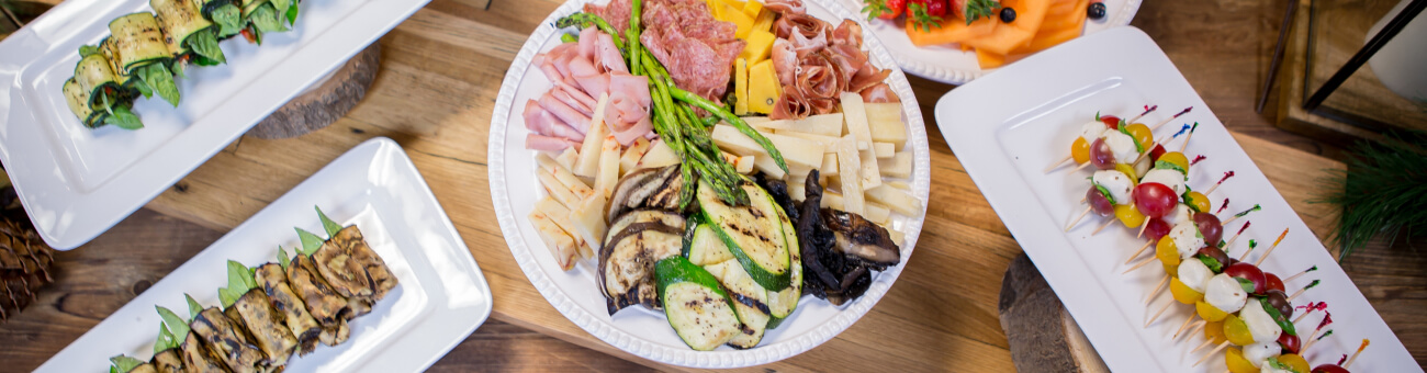 Assortment of platters of meat and cheese appetizers on a table.