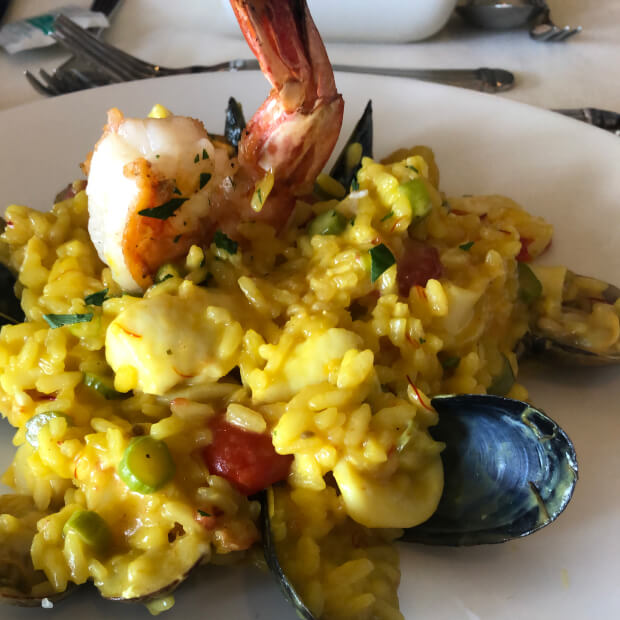 Plate of yellow risotto with shrimp, mussels, and cherry tomatoes.