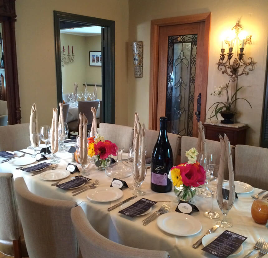 Formal dining room with tablecloths and a magnum size bottle of wine on the table.