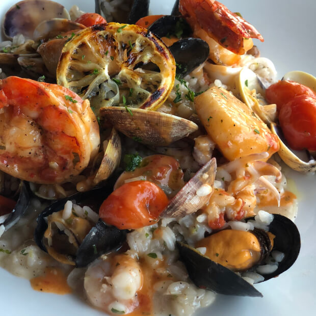 Plate of risotto with shrimp, mussels, and cherry tomatoes.