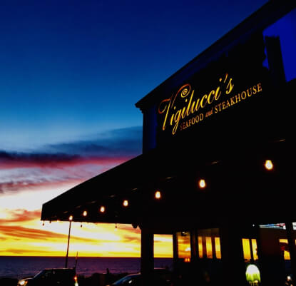 Outside view of Vigilucci's Seafood & Steakhouse at dusk.