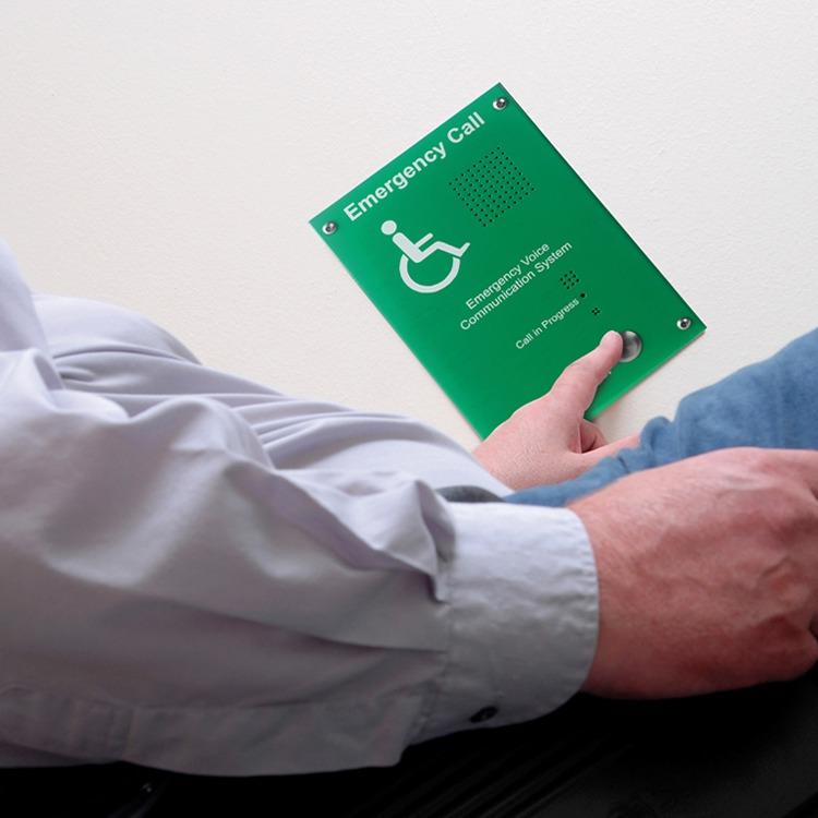Man in wheelchair pressing emergency call button