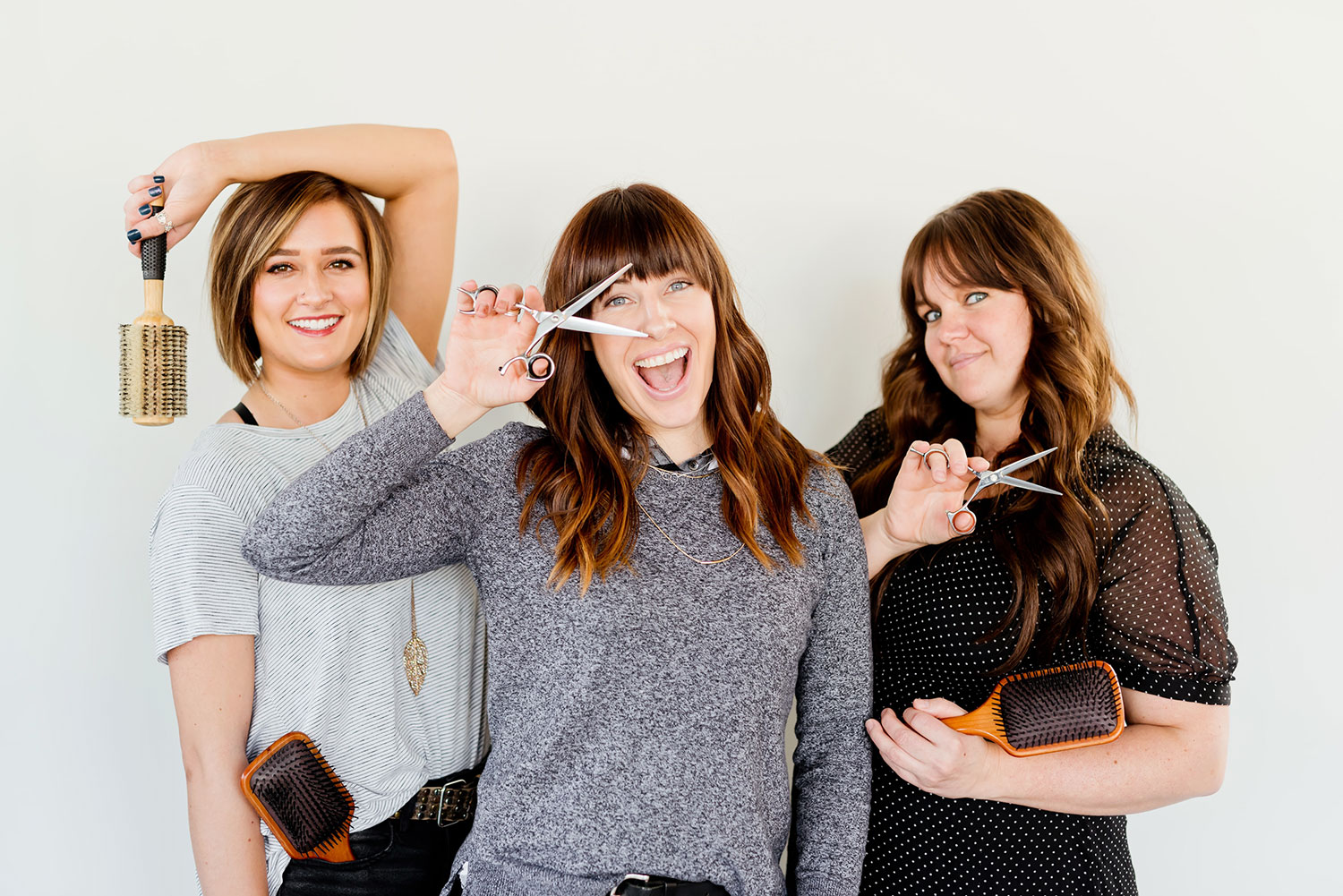 Three smiling hairdressers with scissors