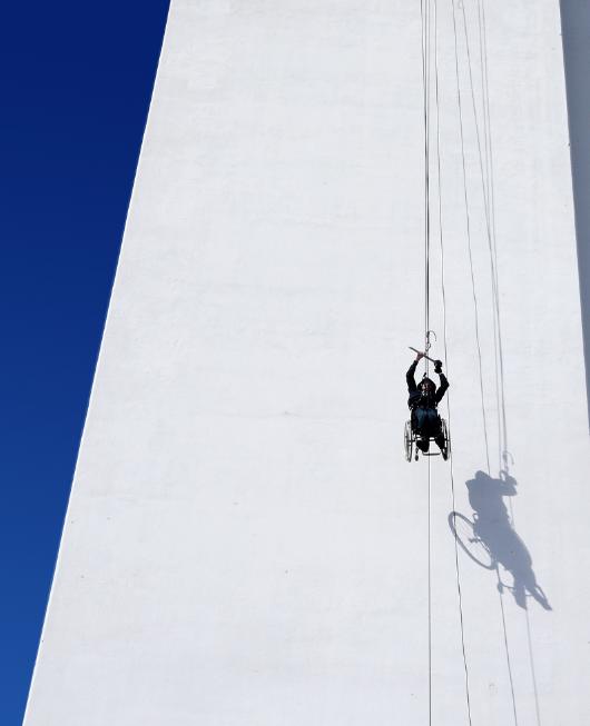 Bilde av rullestolbruker som henger fra en stor høyde.