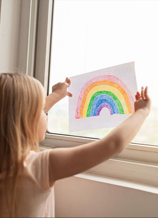 Ei ung jente holder en tegning av en regnbue mot vinduet