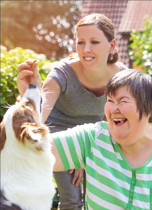 2 mennesker som smiler, de leker med en hund