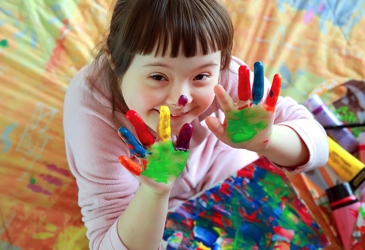 Ei fornøyd jente med maling i forskjellige farger på fingrene etter å ha malt