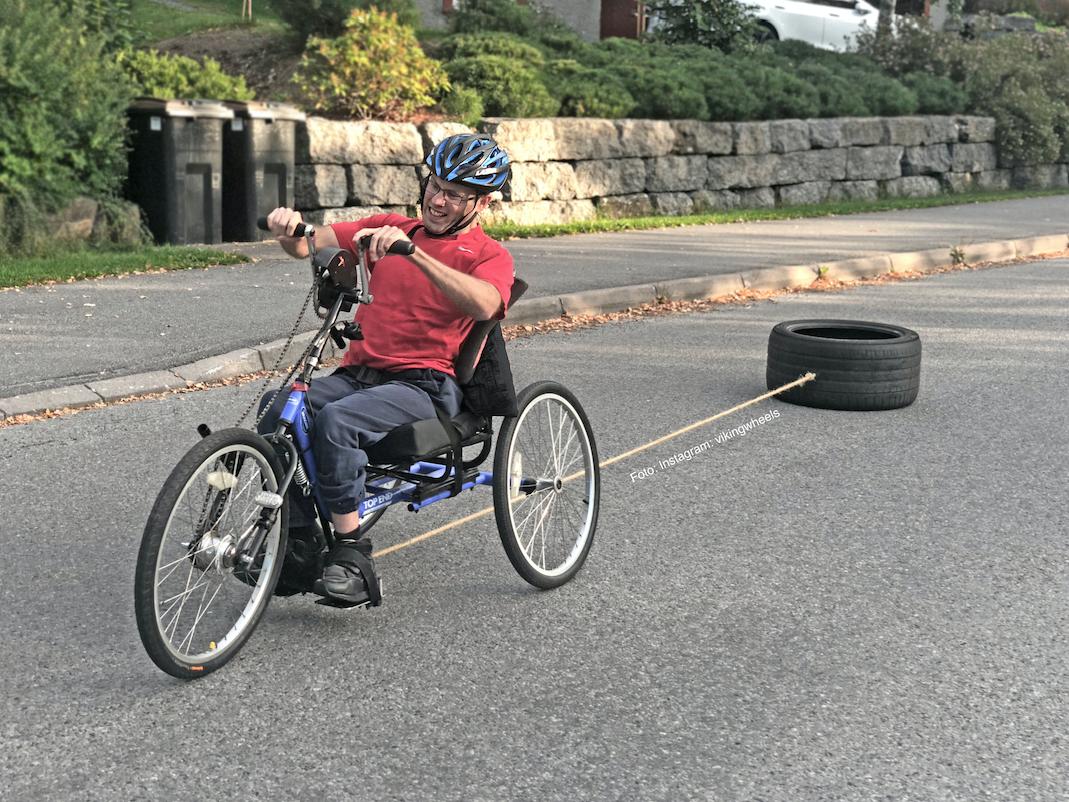 Harald Riise på sykkel med et tungt dekk som henger etter for ekstra vekt