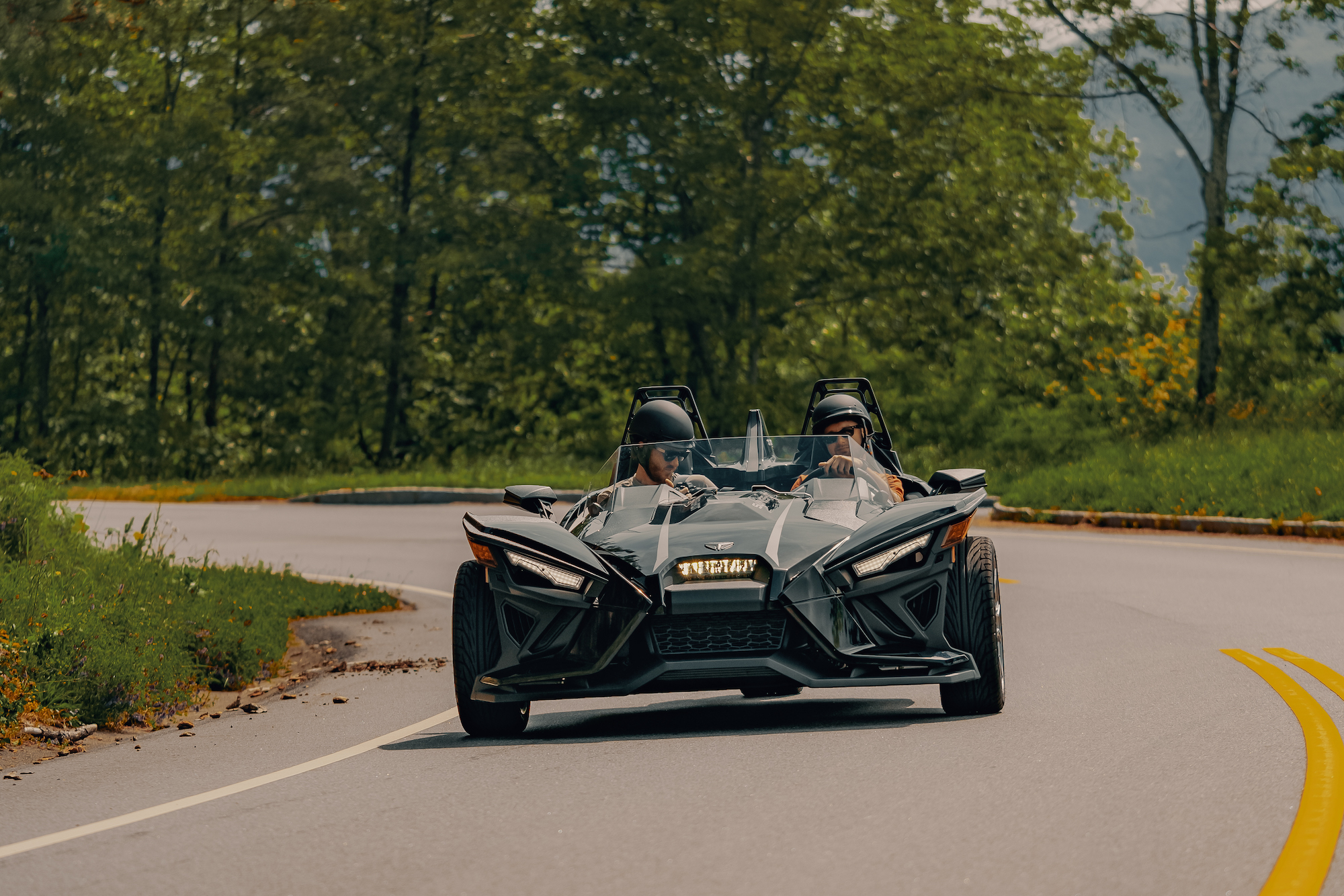 Polaris Slingshot driving down the road around a corner - Polaris Slingshots are available as rentals at the Mountain Mile Mall at Mountain Mile Adventures in Pigeon Forge, Tennessee