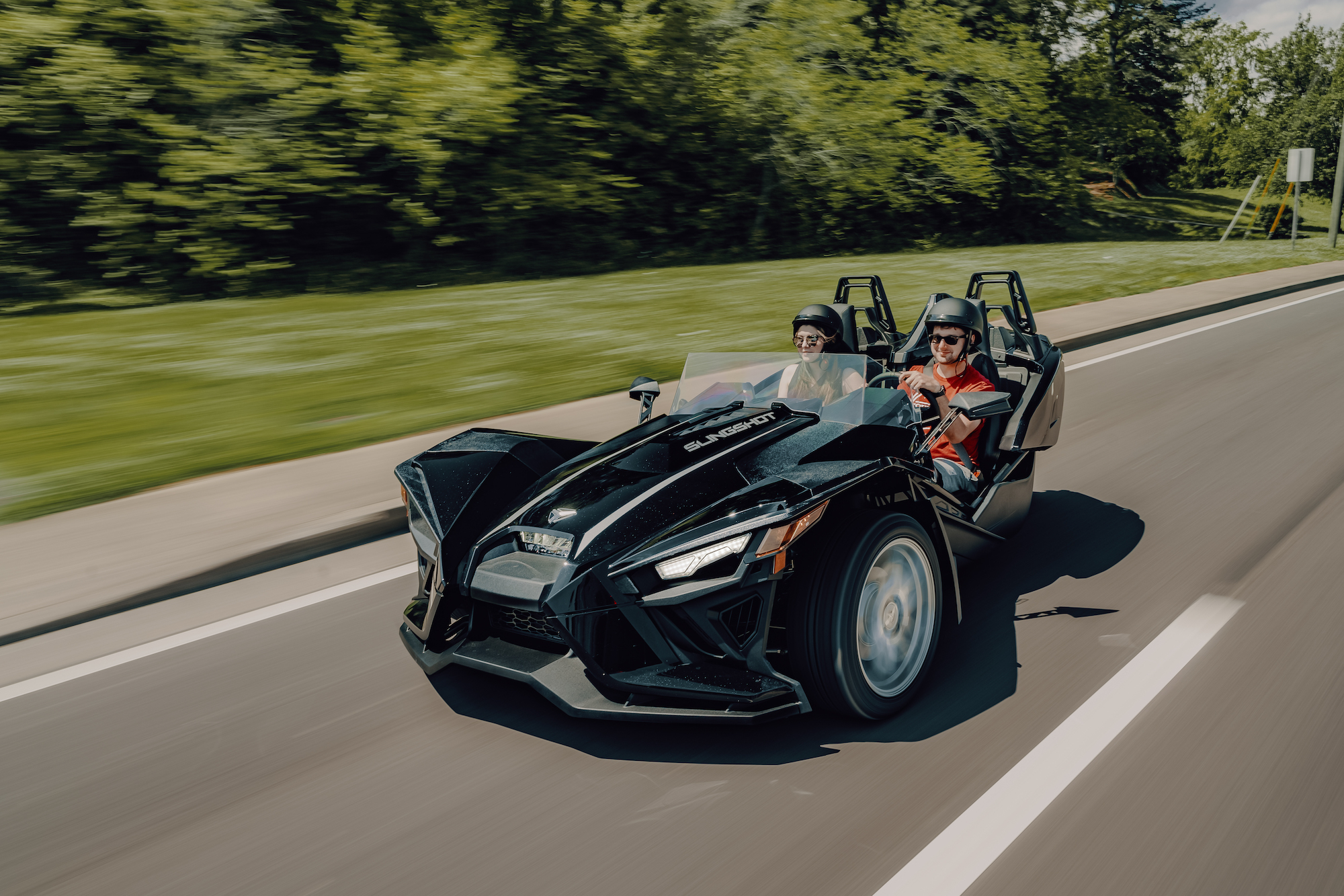 Polaris Slingshot driving down the road - Polaris Slingshots are available as rentals at the Mountain Mile Mall at Mountain Mile Adventures in Pigeon Forge, Tennessee